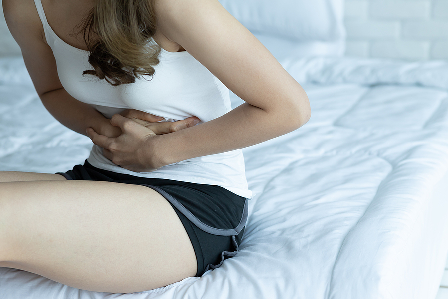 Woman holding her stomach on her bed because of overactive bladder or UTI pain